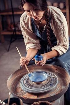 Il maestro ceramista crea un vaso di terracotta su un tornio da vasaio