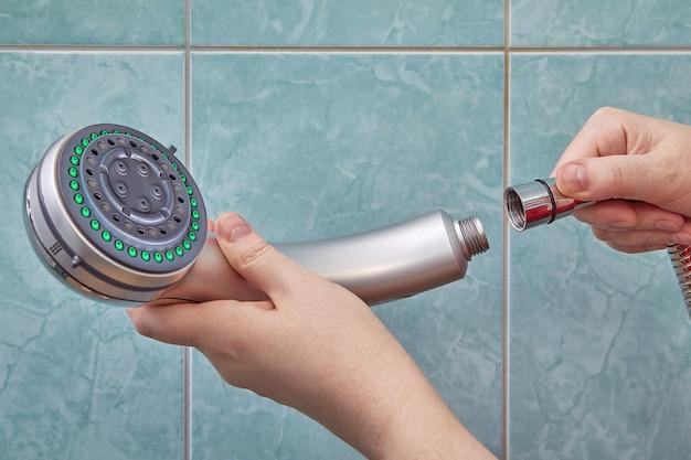 Il maestro cambia il soffione della doccia con uno nuovo in bagno con piastrelle blu sui muri.