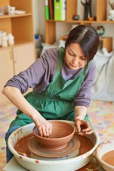 Master class sulla modellazione dell'argilla rossa sul tornio da vasaio nel laboratorio di ceramica.