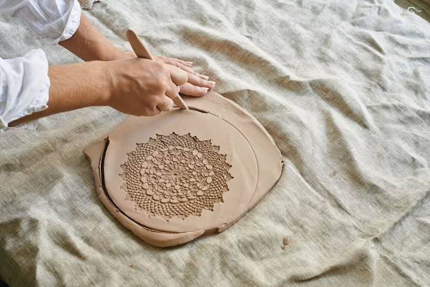Il maestro artigiano fa rotolare l'argilla sul tavolo, trasferisce il modello del tovagliolo sulla massa di argilla
