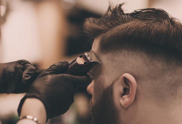 Il maestro taglia un uomo barbuto in un barbiere