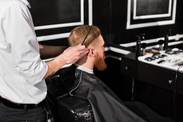 Il maestro taglia barba e capelli nel barbiere. il parrucchiere fa l'acconciatura usando le forbici e un pettine di metallo.