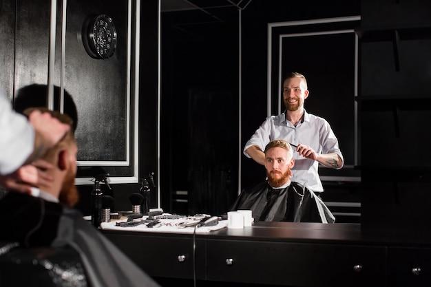 Il maestro taglia i capelli e la barba degli uomini nella bottega del barbiere, il parrucchiere fa l'acconciatura per un giovane