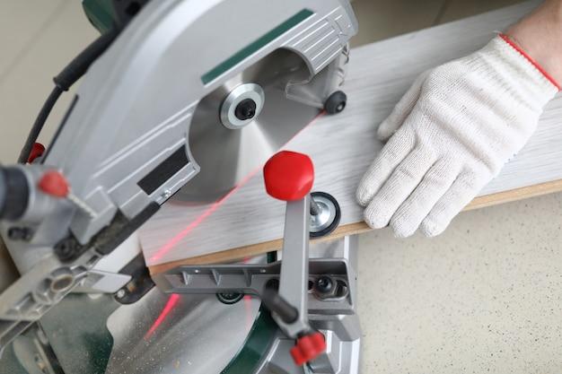 Il maestro taglia il bordo laminato sulla macchina da scrivere