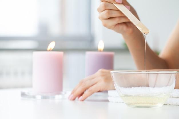 Il maestro esegue l'epilazione delle mani con l'aiuto della cera calda in pasta di zucchero nel salone di bellezza.