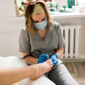 Master durante una pedicure. il processo di pedicure professionale. il concetto di bellezza e salute.