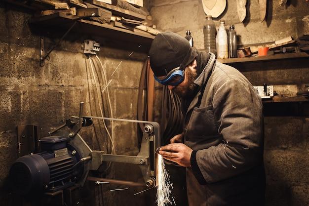 Il maestro macina il coltello su una smerigliatrice a nastro e vengono prodotte molte scintille
