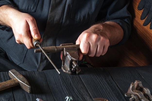 Il maestro macina la parte con un file in una morsa