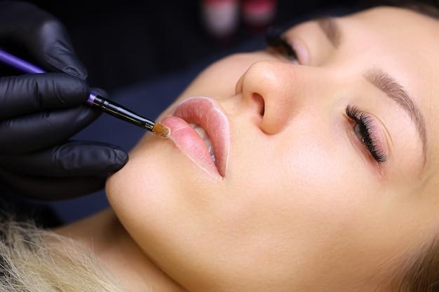 Il maestro tiene un pennello tra le mani e pulisce il contorno delle labbra della modella prima della procedura di trucco permanente delle labbra
