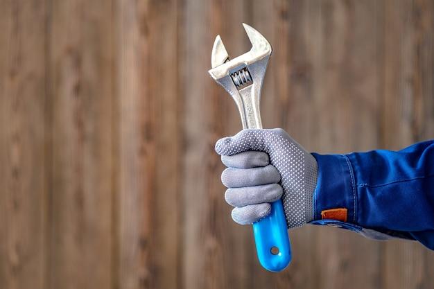 Il maestro tiene in mano una chiave da fabbro regolabile con manico blu. lavori di riparazione del fabbro.