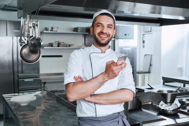 Il maestro della cucina chef felice che cucina in piedi nella cucina commerciale