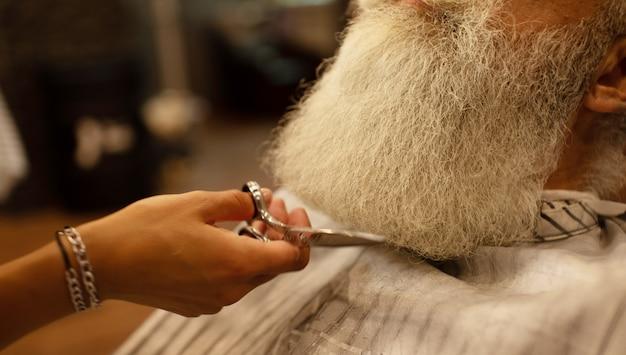 Il maestro esegue la correzione della barba nel salone del barbiere. foto da vicino.
