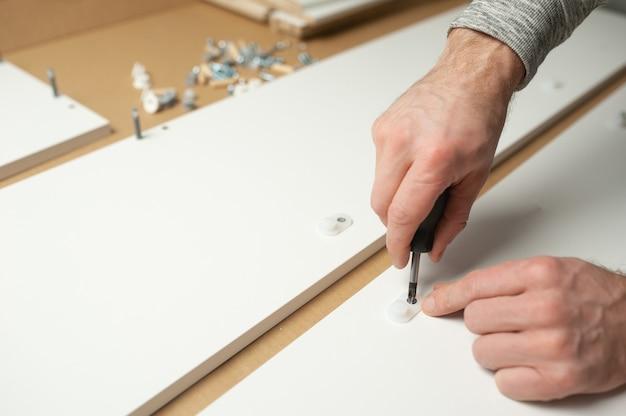 L'uomo maestro installa il montaggio di mobili fai da te. riparazioni a casa
