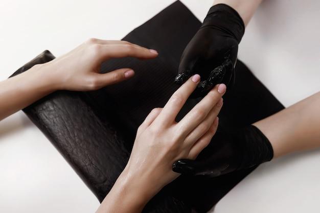 Maestro di manicure in guanti neri, rende client crema idratante e nutriente per massaggi. strutture termali.