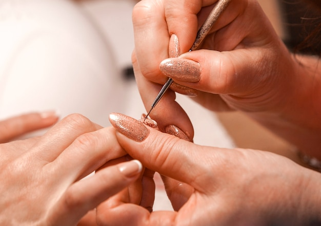 Il maestro della manicure dipinge le unghie