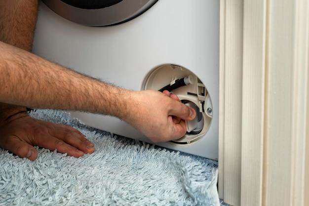 Il master apre il filtro della lavatrice per rimuovere il blocco. problema con il bucato.