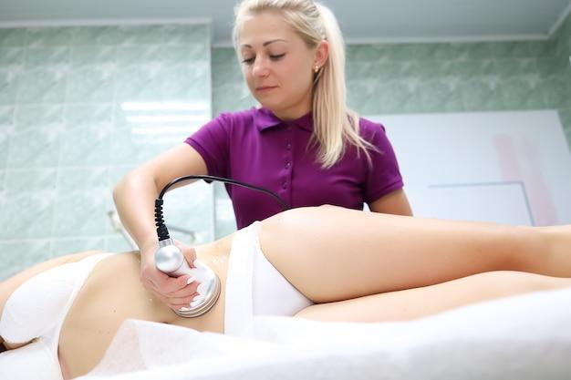 Il maestro esegue un'analisi ad ultrasuoni della cellulite con un dispositivo speciale il modello giace su un fianco di fronte al maestro
