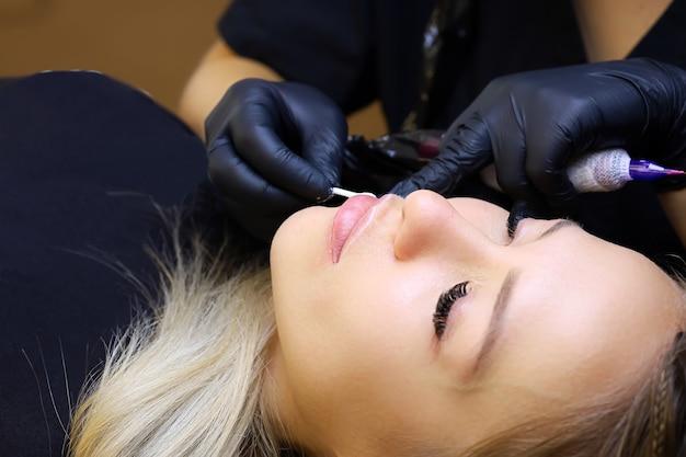 Il maestro del trucco permanente distribuisce l'anestesia con un batuffolo di cotone sulle labbra della modella
