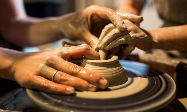 Il maestro vasaio insegna al bambino a lavorare sul tornio da vasaio. immagine ravvicinata.