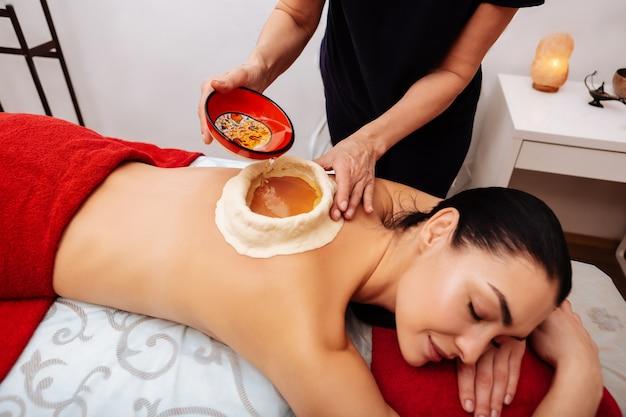 Maestro che versa olio. donna rilassata dai capelli scuri che sperimenta il trattamento ayurvedico in salone mentre il maestro aggiunge olio nella piscina di argilla sulla schiena