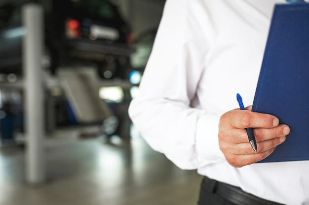 Master receptionist in una stazione di servizio per auto con un tablet per registrare le riparazioni e la manutenzione.