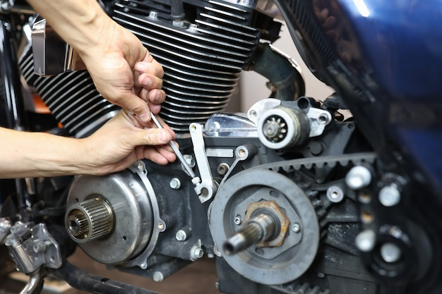 Riparatore maestro che ripara motocicletta in primo piano officina riparazione e manutenzione di motociclette