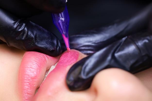 Master s, stringendo il labbro superiore del modello con le dita e - ed esegue il trucco permanente su di esso.