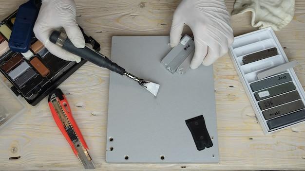 Master sigilla il graffio con cera e un primo piano di saldatore.
