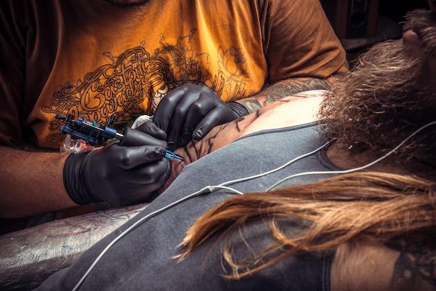 Master che mostra il processo di realizzazione di un tatuaggio in tattoo studio.