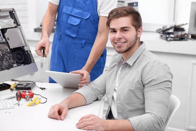 Master che mostra il processo di riparazione al giovane nel centro di assistenza