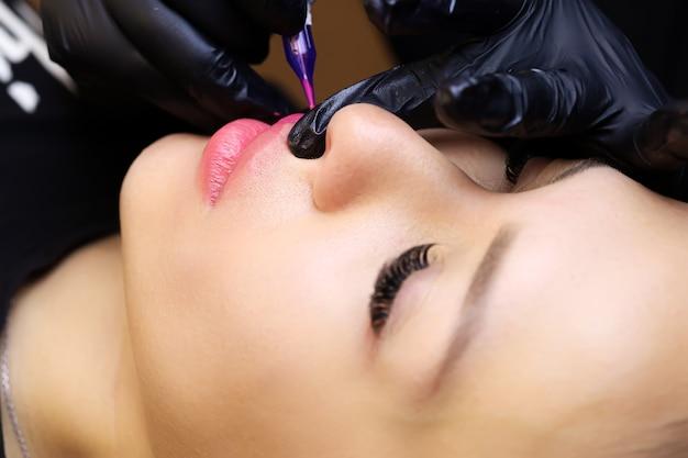 Il maestro stringe le labbra della modella con le dita e applica un tatuaggio rosso sul labbro superiore