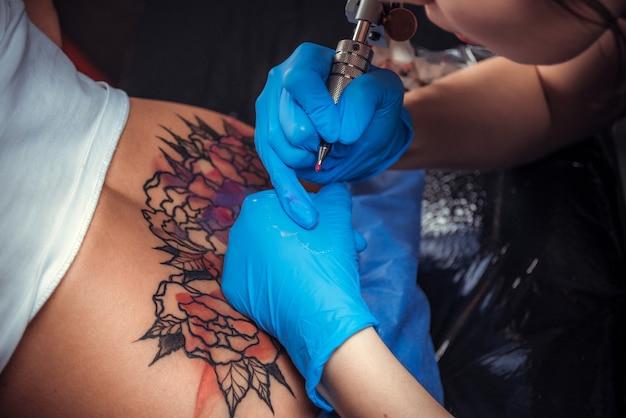 Il maestro tatuatore fa un tatuaggio sulla pelle in studio di tatuaggi.