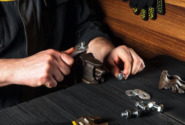Il maestro stringe il dado con una chiave sul primo piano del bullone in un'officina