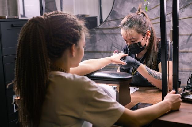 Master utilizza una macchina elettrica per rimuovere lo smalto durante la manicure in salone.