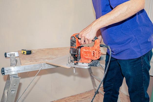 Il maestro usa un seghetto alternativo per tagliare il laminato sul banco da lavoro.