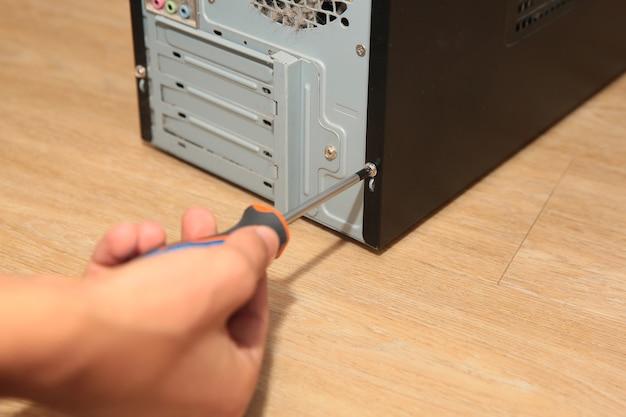 Master con un cacciavite ripara l'unità di sistema del computer