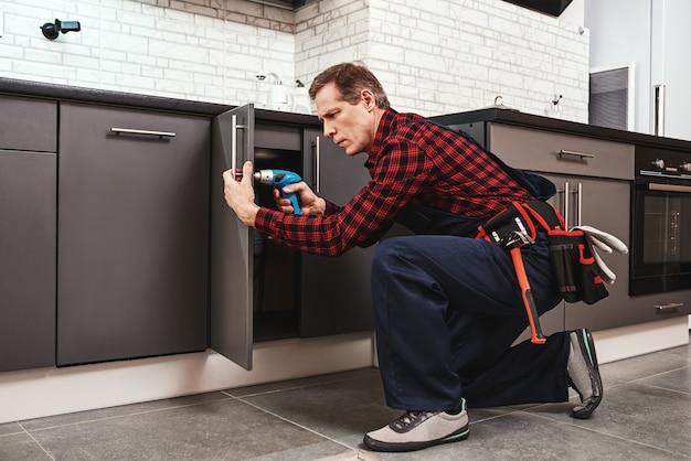 Masterhand lavora a grandezza naturale del tuttofare anziano che ripara l'armadio da cucina kitchen