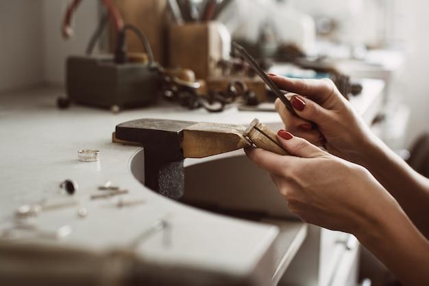 Masters mani vista laterale di un gioielliere femminile mani creando un anello d'argento a lei
