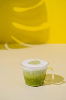 Cappuccino al tè verde matcha in una tazza fondo beige e giallo