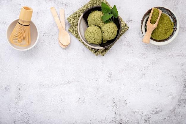 Gelato al tè verde matcha con cono di cialda su pietra bianca.