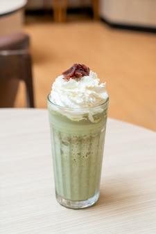 Tè verde matcha latte mescolato con panna montata e fagioli rossi nella caffetteria e ristorante