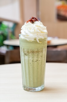 Latte al tè verde matcha mescolato con panna montata e fagioli rossi nella caffetteria e nel ristorante