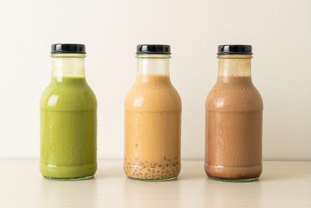 Tè verde matcha latte, cioccolato e tè al latte con gelatina di budino in bottiglia di vetro sul tavolo