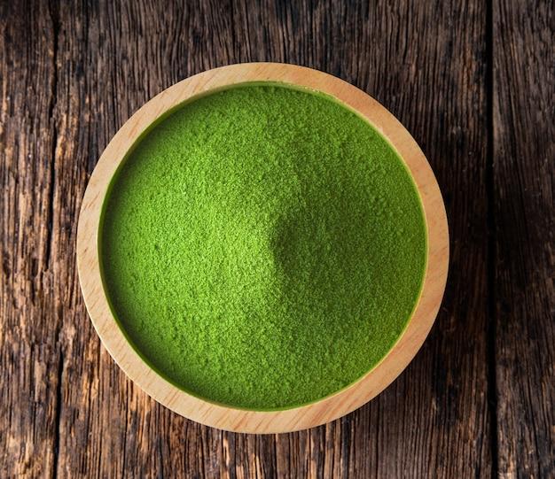 Polvere di tè verde matcha in una ciotola sul tavolo di legno
