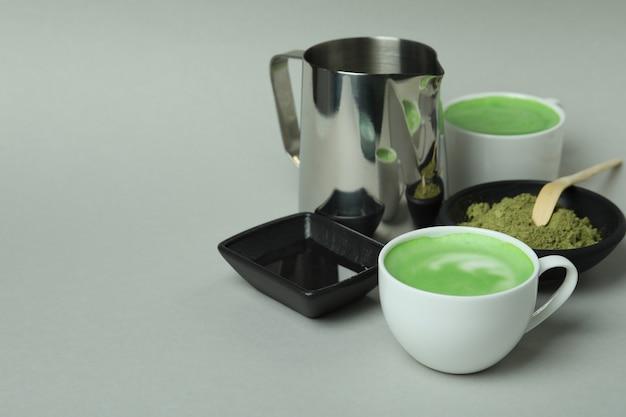 Matcha latte e accessori per fare su sfondo grigio chiaro