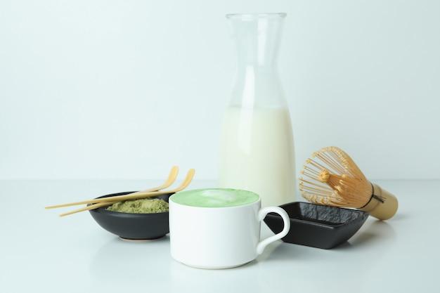 Matcha latte e accessori per fare sul tavolo bianco