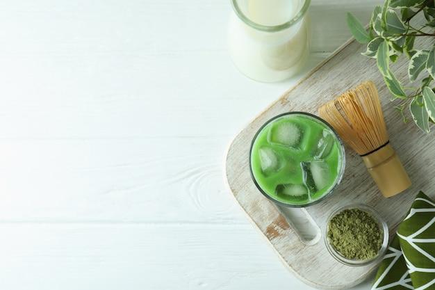 Matcha latte e accessori per fare sul tavolo di legno bianco