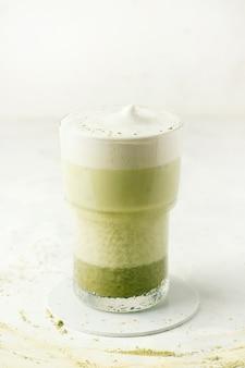 Matcha latte su un piatto bianco. foto verticale. copia spazio