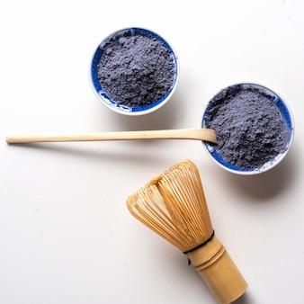 Tè matcha blu in polvere, frusta e cucchiaio di legno isolato su bianco