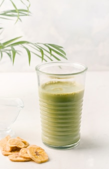Tè matcha in un bicchiere su uno sfondo bianco. colazione salutare
